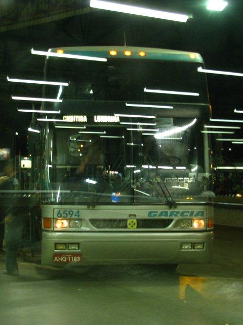 Foto feita por trás de vidro, sob diversos reflexos da iluminação artificial.