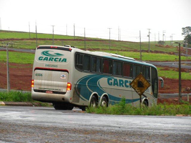 Ônibus parcialmente encoberto por placa de sinalização.